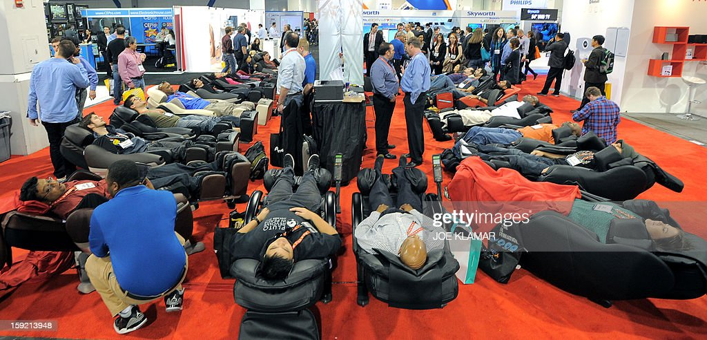 Consumers relax in massage chairs at Inada booth at the 2013 International CES at the Las Vegas Convention Center on January 9, 2013 in Las Vegas, Nevada. CES, the world's largest annual consumer technology trade show, runs from January 8-11 and is expected to feature 3,100 exhibitors showing off their latest products and services to about 150,000 attendees.AFP PHOTO / JOE KLAMAR