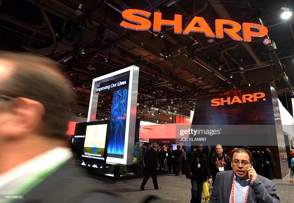 Consumers walk by SHARP booth at the 2013 International CES at the Las Vegas Convention Center on January 10, 2013 in Las Vegas, Nevada. CES, the world's largest annual consumer technology trade show, runs from January 8-11 and is expected to feature 3,100 exhibitors showing off their latest products and services to about 150,000 attendees.AFP PHOTO / JOE KLAMAR