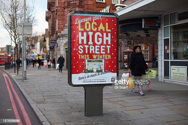 Consumers walks past a billboard promoting Christmas shopping on local high streets on Lewisham high street on December 5 2012 in London England The...