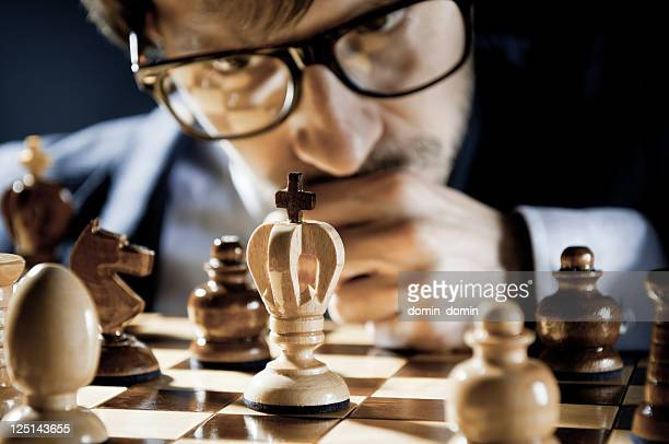 Consummate, focused Chess Player in glasses thinking on next move