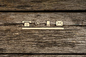 Contact and communication icons, telephone, at sign, mobile and mail, on textured rustic wooden boards.
