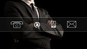 Contact icons over image of the torso of a businessman standing with folded arms in a classic black suit.
