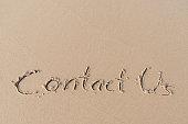 'Contact Us' message written on sand beach