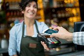 Contactless payment at a restaurant with close-up on the cell phone over an eftpos machine