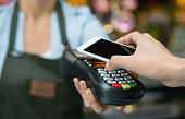 Close-up on a contactless payment at a restaurant with cell phone over an eftpos machine