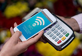 Close-up on a contactless payment with cell phone over an eftpos machine. Design on screen is own design.