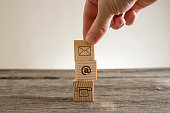 Hand placing little wooden cube on stack over table with email and phone pictograms, business contacts conceptual figure.