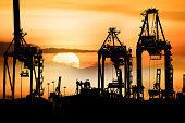 Container Cargo freight ship with working crane bridge in shipyard at Silhouette With sunset, Logistic Import Export background concept.