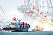 Container cargo ship entering the port with harbor crane background. Freight Transportation. Logistic Import Export background concept.