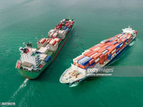 container cargo ship  in green sea ship sailed in opposite directions , aerial view .