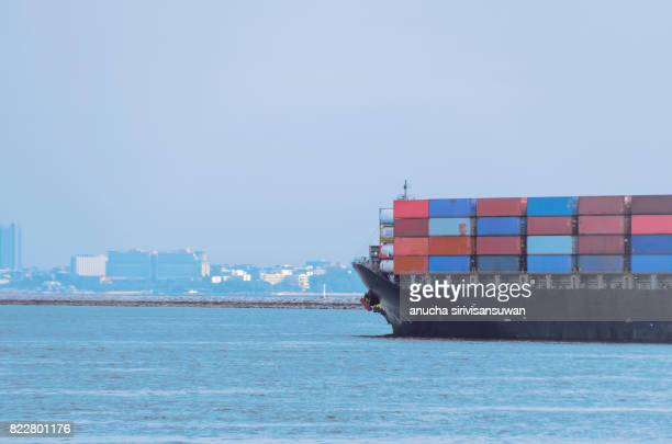 container cargo ship in sea with city .