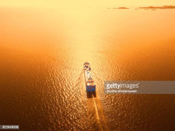 container cargo Ship is running in sea orange light .