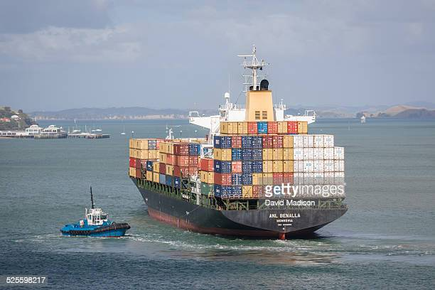 A container cargo ship maneuvers in Auckland Harbor assisted by a tug boat Auckland New Zealand January
