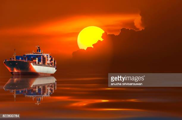container cargo ship reflect in water with sunset background .