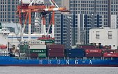 A container is transferred from a freighter at the pier at the port in Tokyo on July 25 2016 Japan on July 25 posted its first halfyear trade surplus...