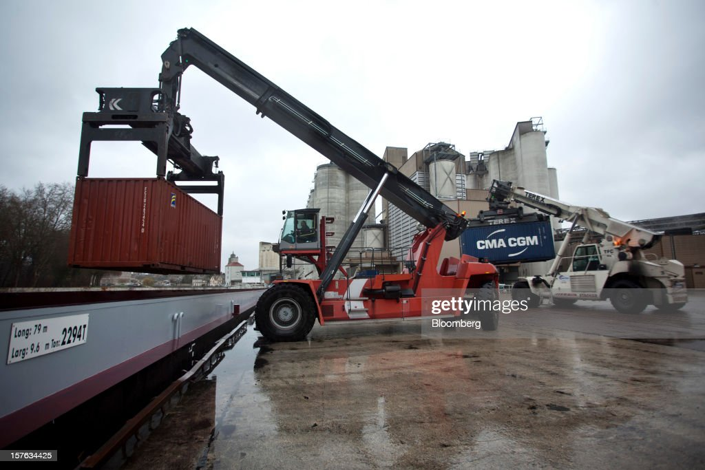 Container lifters hoist shipping containers containing cereal grain onto barges on the dockside at the Groupe Soufflet plant in Nogent-sur-Seine, France, on Tuesday, Dec. 4, 2012. European Union corn imports may be the second-highest on record this season after drought parched crops and a surge in wheat exports curbed domestic grain supply. Photographer: Balint Porneczi/Bloomberg via Getty Images