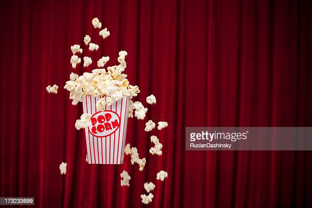 A container of popcorn spilled on a red curtain