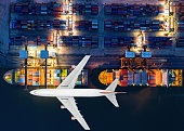 Container ship and transport aircraft in export and import business and logistics. Shipping cargo to harbor by crane. Water transport International. Aerial view and top view.