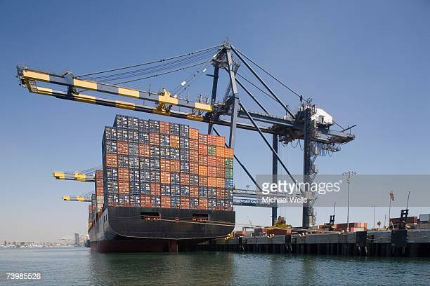 Container ship below cranes at a commercial dock