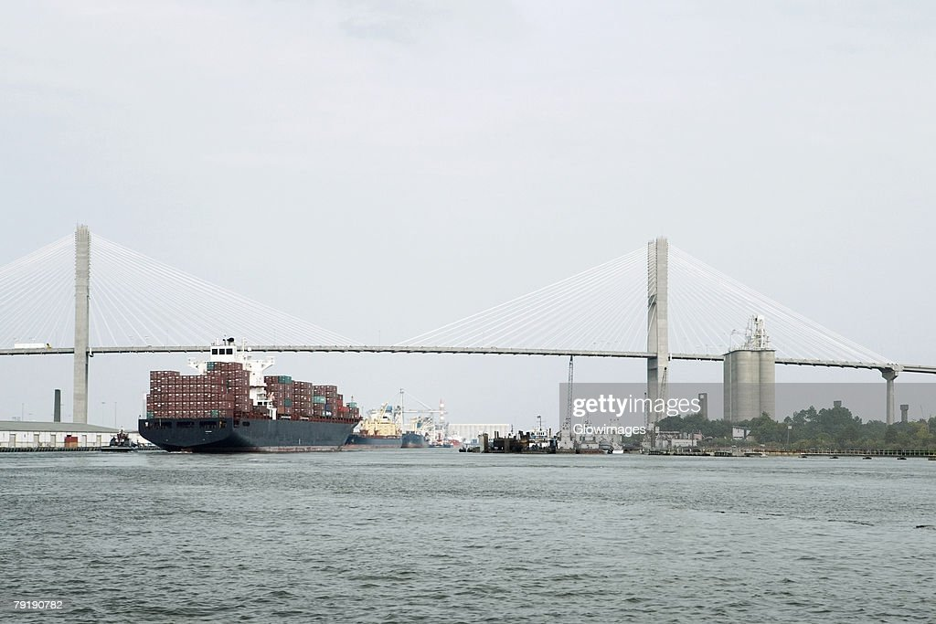 Container ship in a river with a suspension bridge in the background, Talmadge Bridge, Savannah River, Savannah, Georgia, USA : Foto de stock