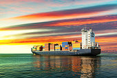 Sailing container ship at sunset on sea.