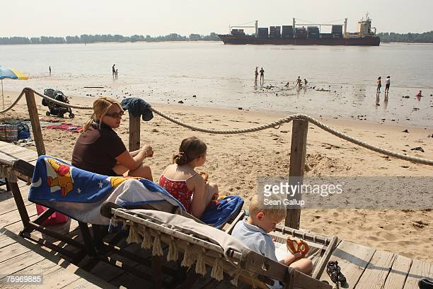A container ship passes beachgoers on the Elbe River on its way to Hamburg August 4 2007 at Wedel Germany Northern Germany with its busy ports of...