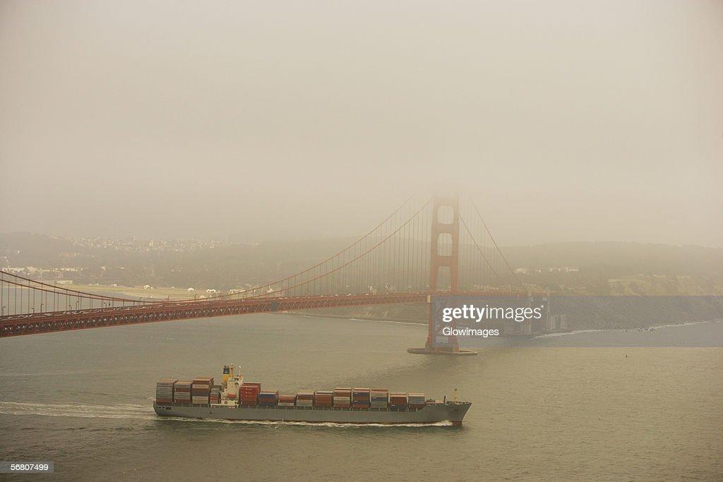 Container ship passing under a bridge, Golden Gate Bridge, San Francisco, California, USA : Stock Photo
