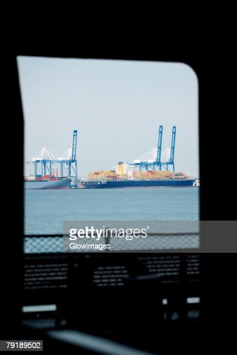 Container ships docked at a commercial dock viewed through the window of a ship, Patriot's Point, Charleston Harbor, Charleston, South Carolina, USA : Stock Photo