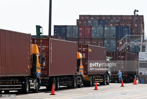 Container trucks wait beside the Oi container yard of the Tokyo port in Tokyo on September 8 2017 Japan's economy grew 06 percent in the second...