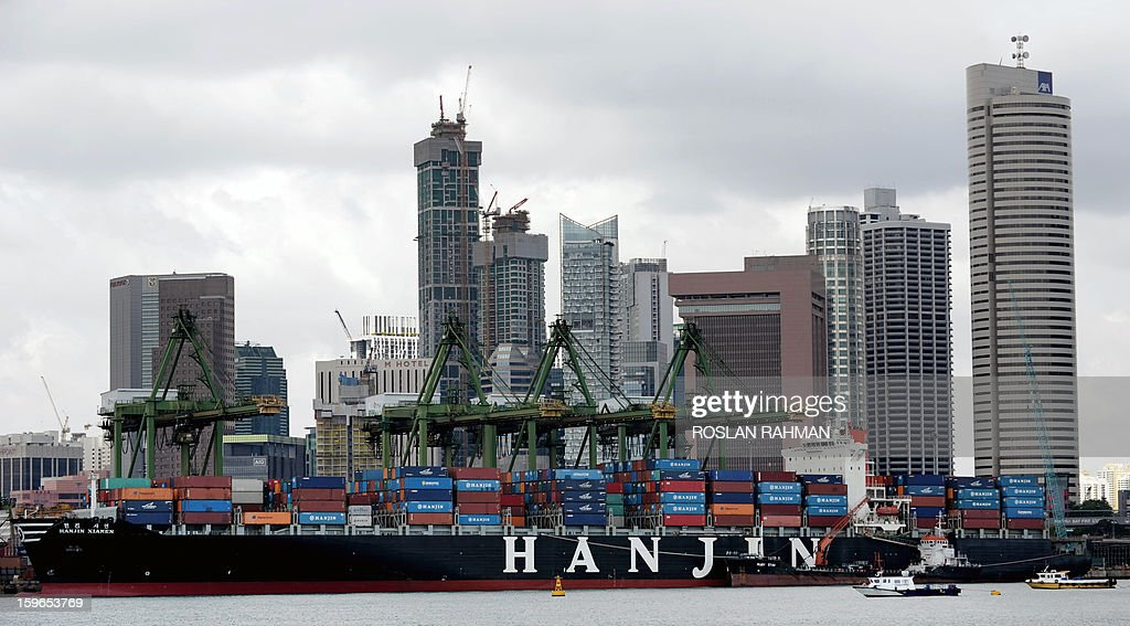 A container vessel sits docked at the Keppel terminal in Singapore on January 18, 2013. Singapore escaped a technical recession after the economy grew in the fourth quarter thanks to a boost from services, government data showed earlier this month, but prospects for 2013 remain gloomy.