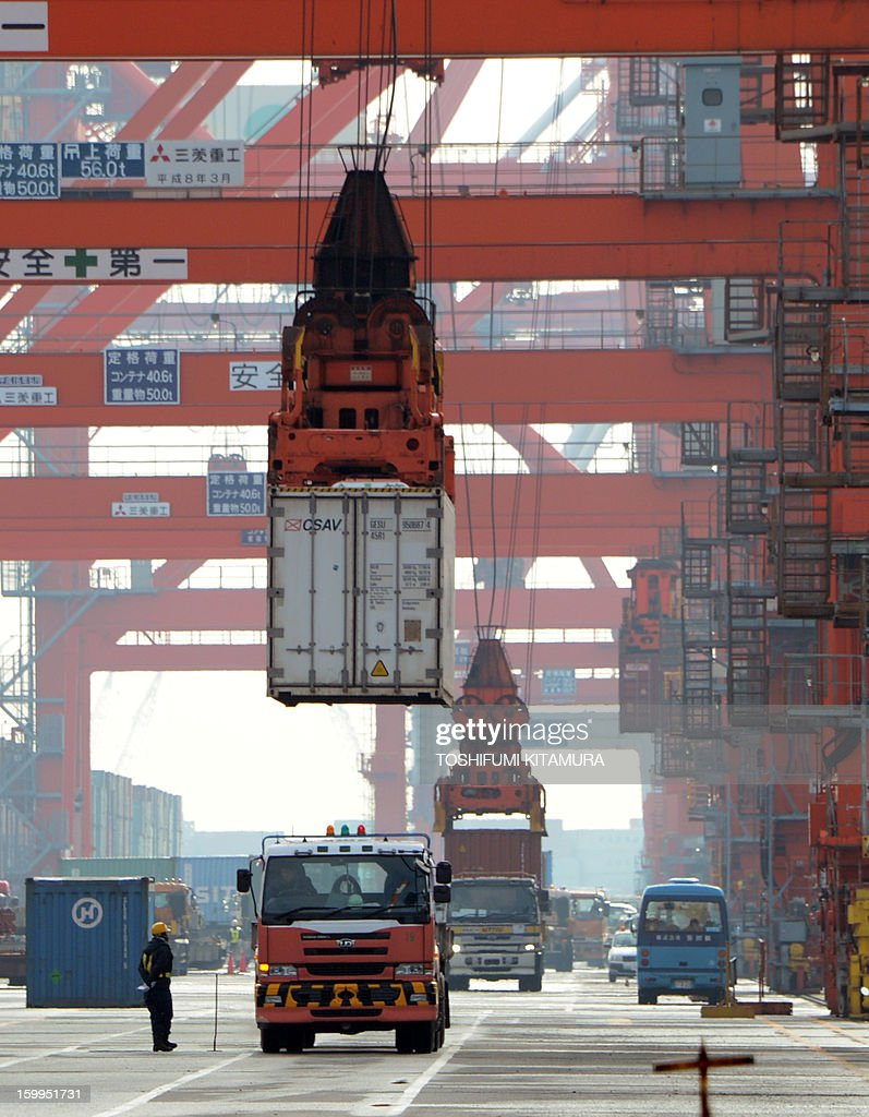 Containers are loaded onto a freighter at the pier in Tokyo port on January 24, 2013. Japan said it logged a record trade deficit in 2012, Japan's exports totalled 63.7 trillion yen against imports of 70.7 trillion yen, as exports to debt-hit Europe plunged and a bitter diplomatic spat with its biggest trade partner China weighed on demand. AFP PHOTO / TOSHIFUMI KITAMURA