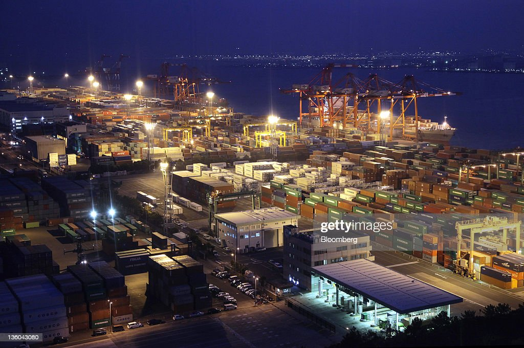 Containers are stacked at a shipping terminal at night in Tokyo Japan on Wednesday Dec 21 2011 Japan's exports fell and the central bank lowered its...