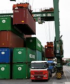 Containers are transferred onto the trucks at an international container pier at the port in Tokyo on July 25 2016 Japan on July 25 posted its first...