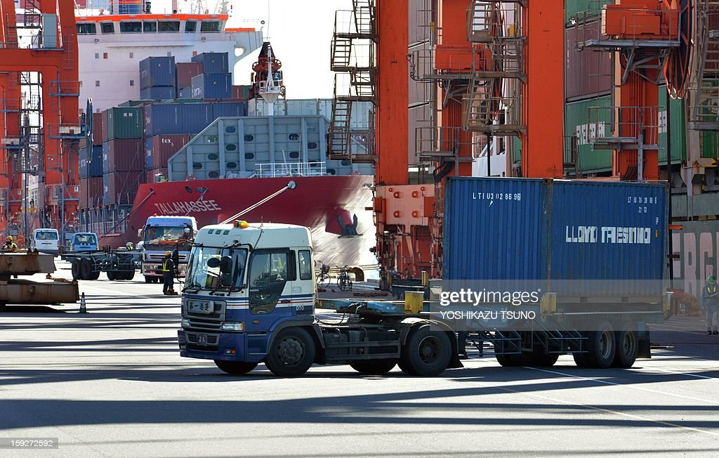 Containers are unloaded from international freighters at an international cargo terminal at Tokyo's port on January 11, 2013. Japan fell into a huge 2.5 billion USD current account deficit in November as exports to China and debt-hit Europe slumped. AFP PHOTO / Yoshikazu TSUNO