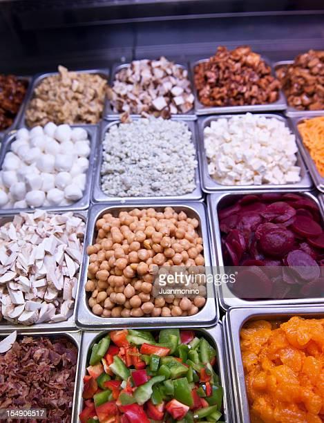 Conteneurs de différents aliments sur un bar à salades.