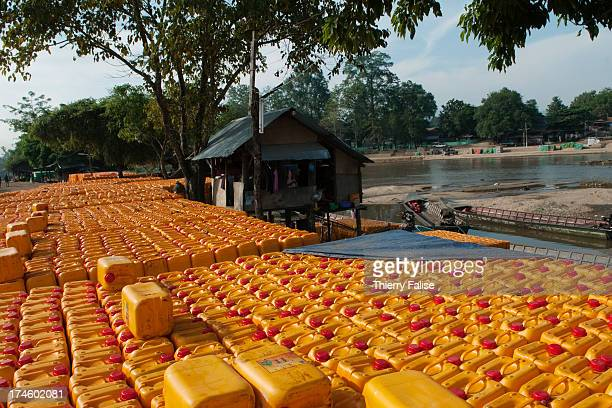 Containers of palm oil made in Malaysia are waiting along the Moei River marking the border between Thailand and Myanmar to be shipped to Myanmar...