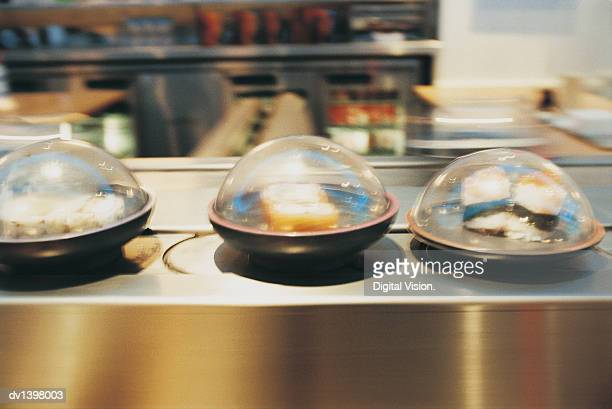 Containers of Sushi in a Line on a Conveyor Belt in a Restaurant