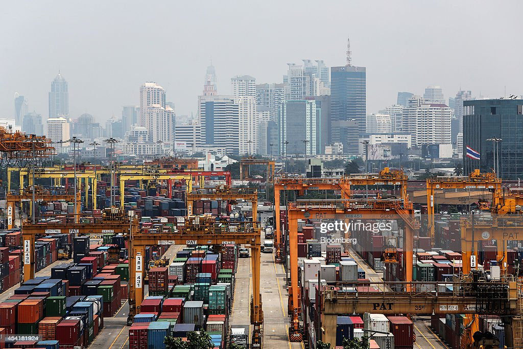 Containers sit stacked near gantry cranes at the Port of Bangkok as high rise buildings stand in the background in Bangkok, Thailand, on Monday, Aug. 25, 2014. Thailand's trade figures are scheduled for release on Aug. 27. Photographer: Dario Pignatelli/Bloomberg via Getty Images