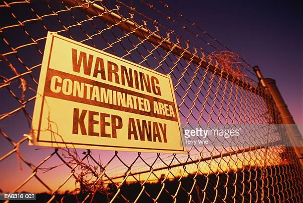 'Contaminated Area' warning sign on chain-link fence