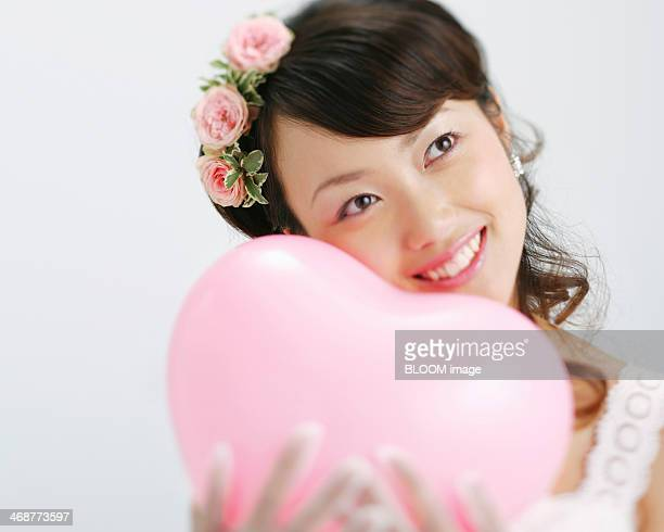 Contemplated Bride Holding Heart Shape Balloon