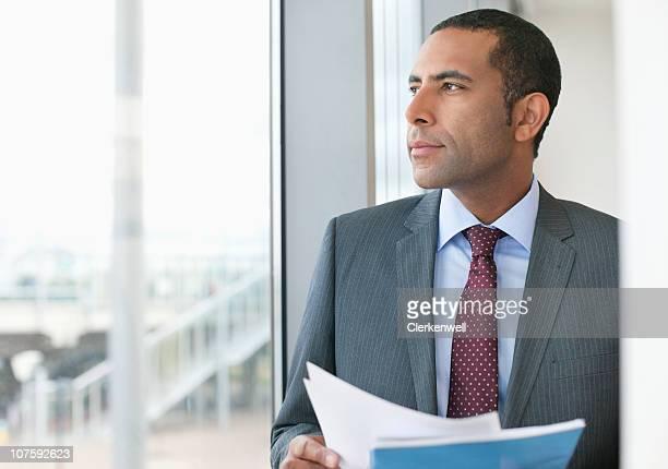 Contemplative Homme d'affaires avec le document à proximité de la baie au bureau verrouillé