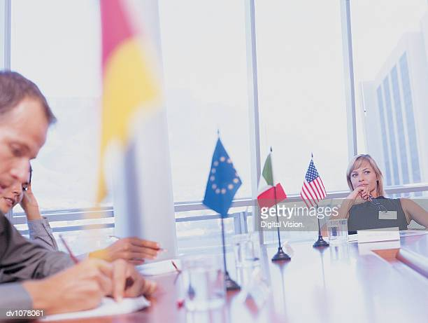 Contemplative Businesswoman Sitting at the End of a Conference Table in a Meeting