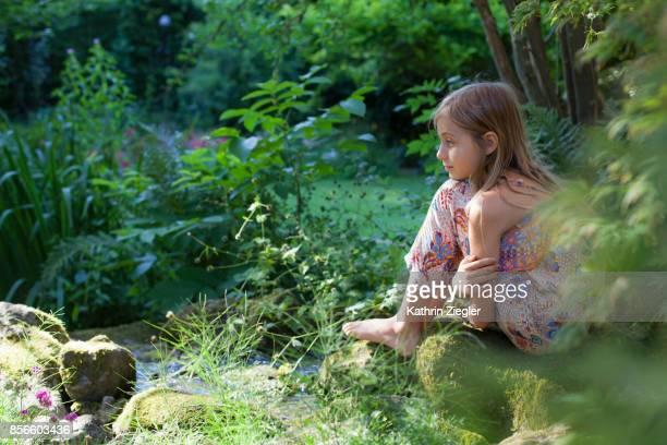 Contemplative little girl sitting on a rock in garden