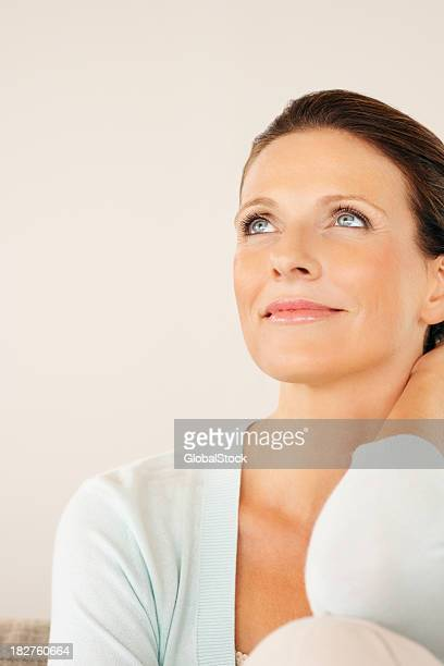 Contemplative mature lady looking up at copy space