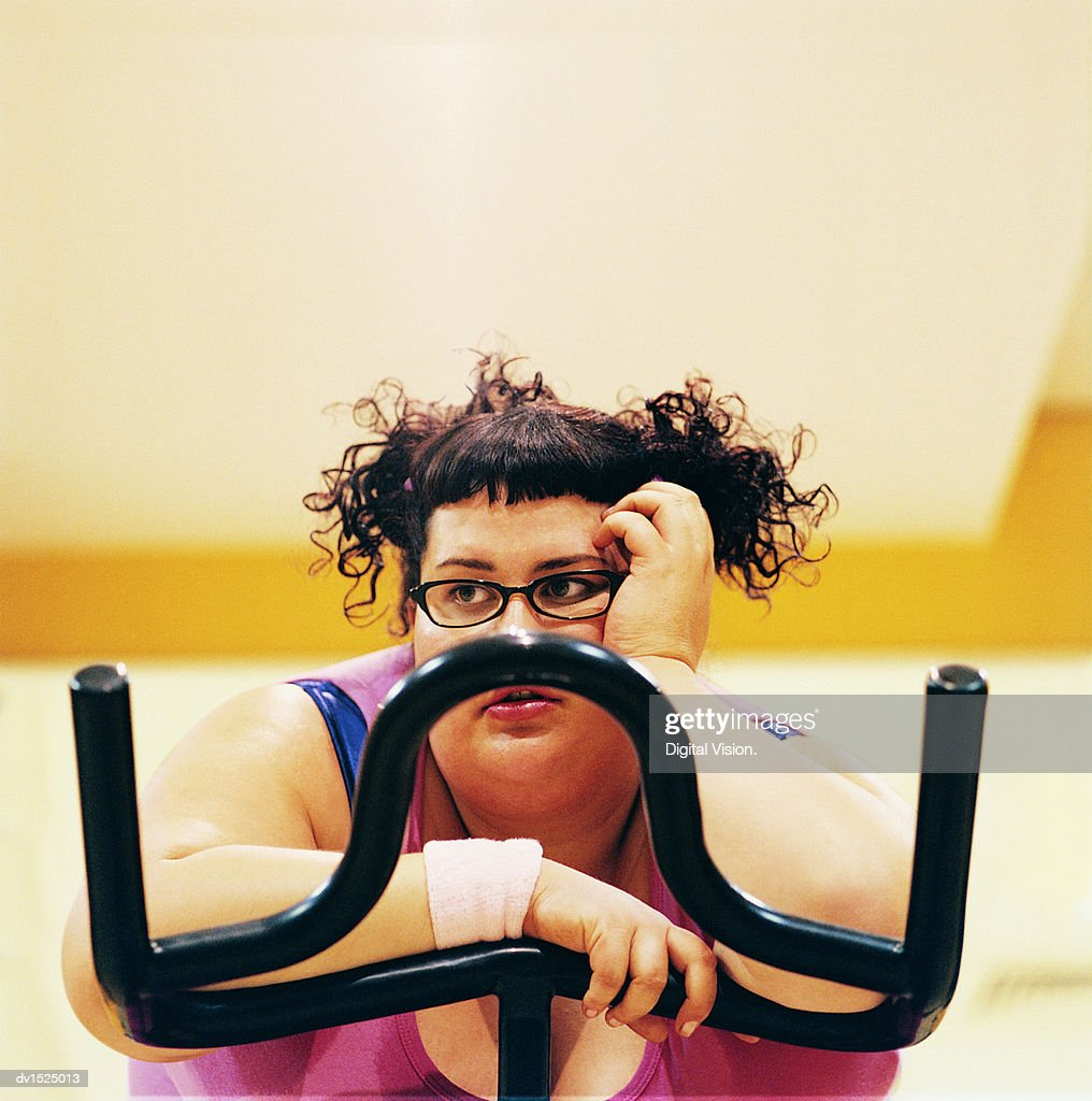 Contemplative Overweight Woman on an Exercise Bike in the Gym : Stock Photo