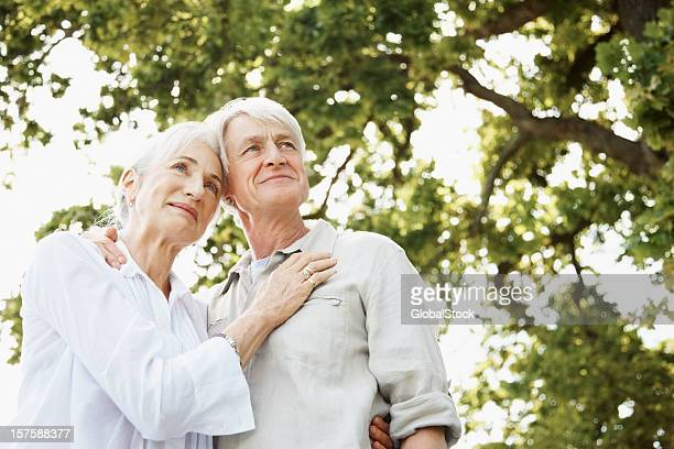 Contemplative Senior Couple Standing Together Under Tree