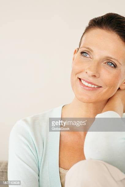 Contemplative smiling mature lady sitting isolated