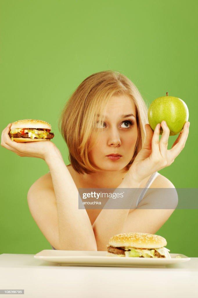 Contemplative Woman Holding Apple and Hamburger Deciding : Stock Photo