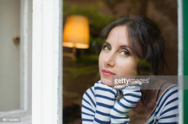 Contemplative woman looking out of window