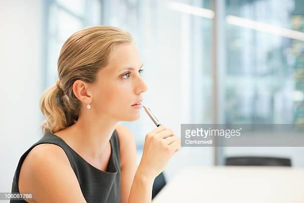 Entspannte junge Geschäftsfrau holding Stift, Seitenansicht